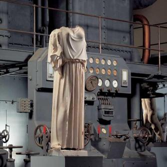 Statue dressed in a peplos in front of a diesel engine