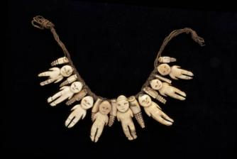 Human-shaped figures and pendants of whale ivory strung on fine plaited coir cords. Probably presented to Lady Gordon, 1875 - 80, Fiji.