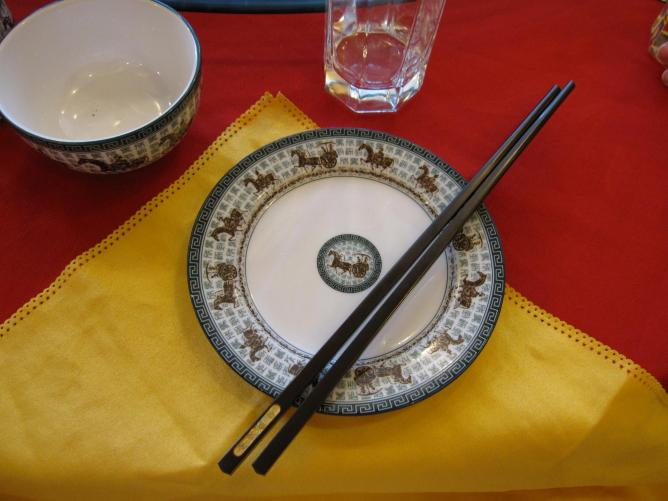 Plate and chopsticks on a yellow napkin and red table cloth |