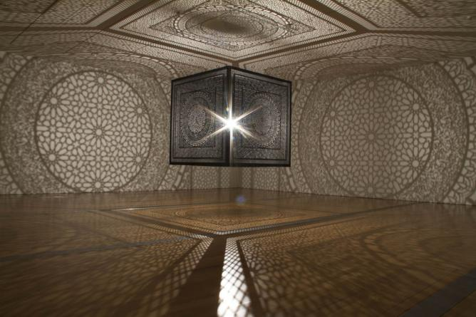 Anila Quayyum Agha, 'Intersections', completed in 2013, laser-cut wood, single light bulb, 6.5 inches square cube. Installation view at Grand Rapids Art Museum, 2014 | Courtesy the artist