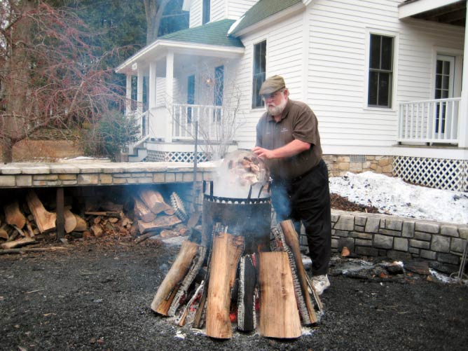 A White Gull Inn employee begins the traditional Door County-style fish boil | © Mark Baylor/Flickr