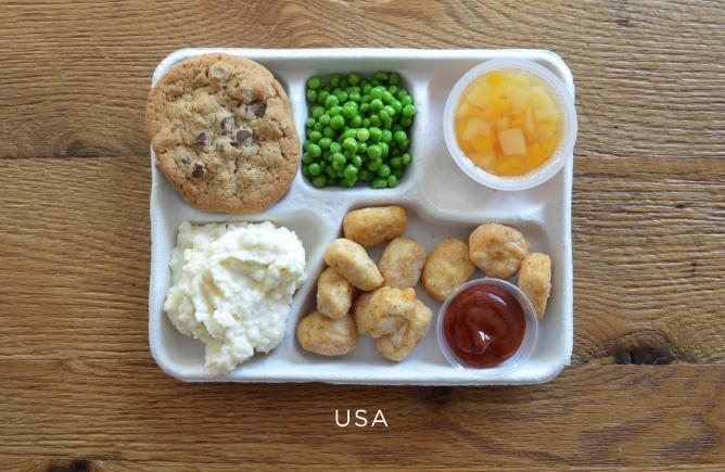 Fried 'popcorn' chicken, mashed potatoes, peas, fruit cup and a chocolate chip cookie