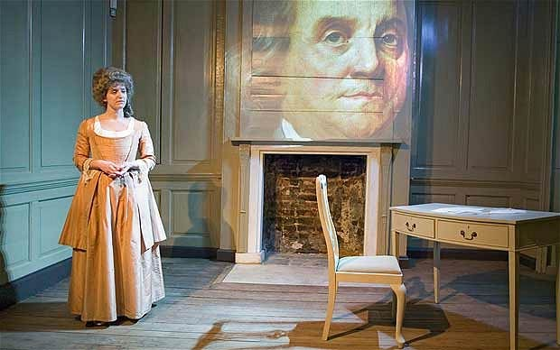 Woman standing in period dress with a projection of Benjamin Franklin over the Fireplace