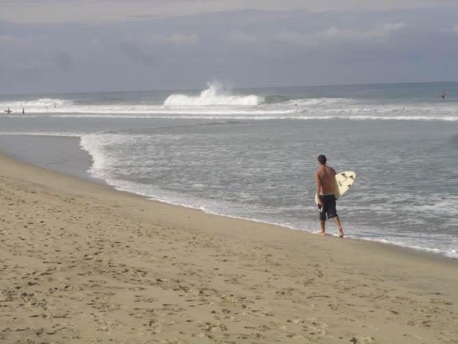 Surfer walking down the beach of Puerto Escondido