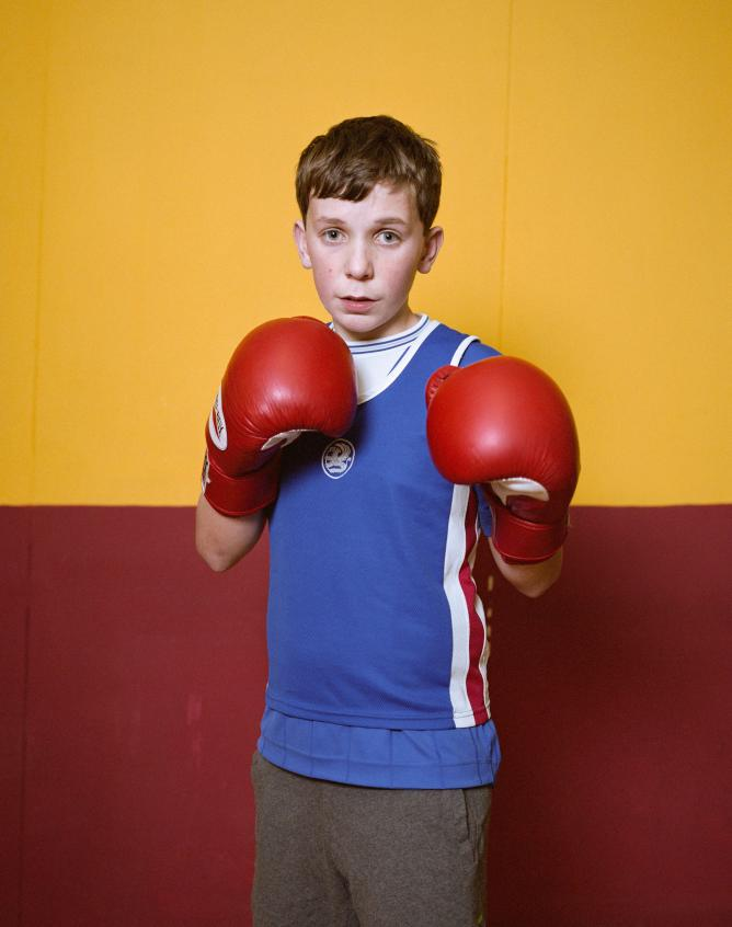 Young boy wearing boxing gloves