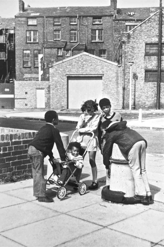 Young children childminding a baby in black and white