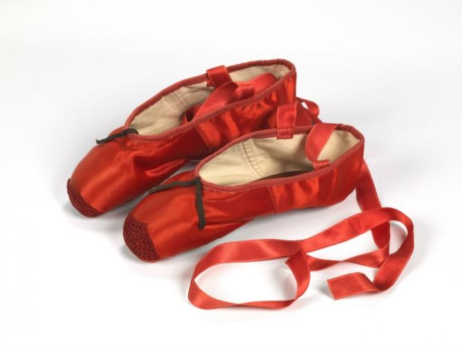 Red ballet shoes made for Victoria Page (Moira Shearer) in The Red Shoes (1948), silk satin, braid and leather, England. Artist: Freed of London founded in 1929. Photo: ©Northampton Museums and Art Gallery.
