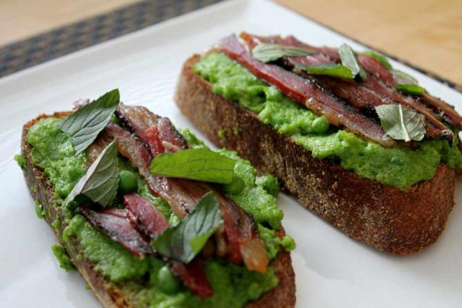Two Slices of the menu item Peas and Bacon on toast sit on a plate at the restaurant Vernick Food & Drink in Philadelphia.