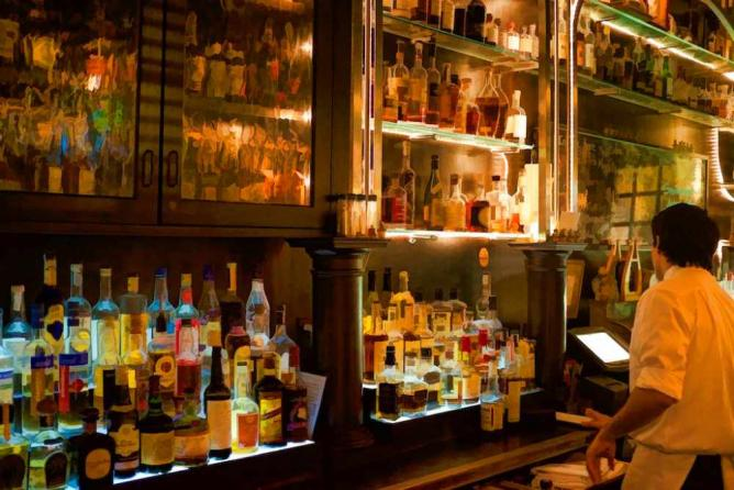 A bartender stand behind the bar at Village Whiskey where an array of liquor sits.