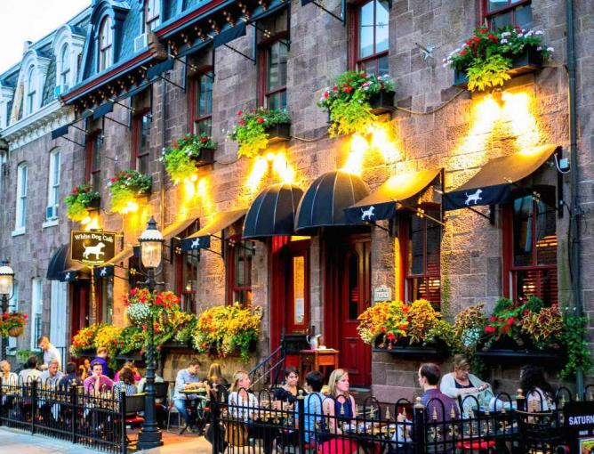 Diners sit outside of White Dog Cafe on a beautiful summer evening.