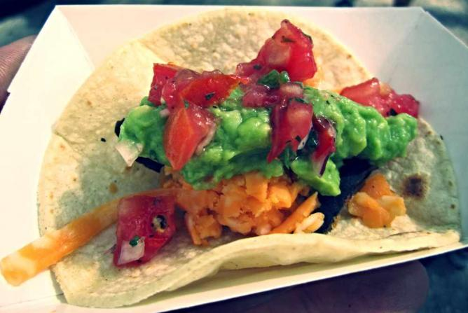 An Honest Tom Taco with its vibrant colors and fresh ingredients sits in a paper food holder.
