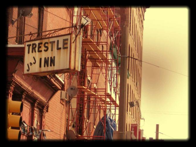 An outside shot of the Trestle Inn's sign and red outer facade standing from the Northeast corner of 11th and Callowhill St looking south.