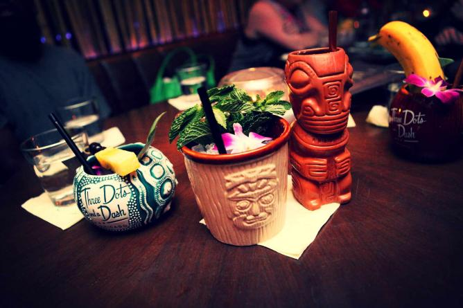 Cocktails are served in tropical glasses like skull and tiki heads at Three Dots and a Dash.