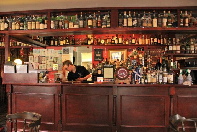 Whisky and Scotch bottles go all the way around the restaurant in alphabetical order @ Fiddler's