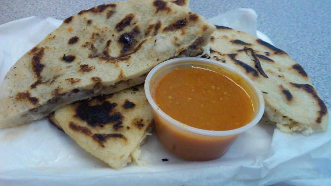 Pupusa, cut in half with peppery hot sauce   © C. Marie Cradle