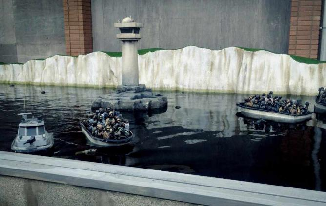 One of the installation's 'games': model immigration and police boats floating on an ornamental lake   Courtesy of Marianna Hunt