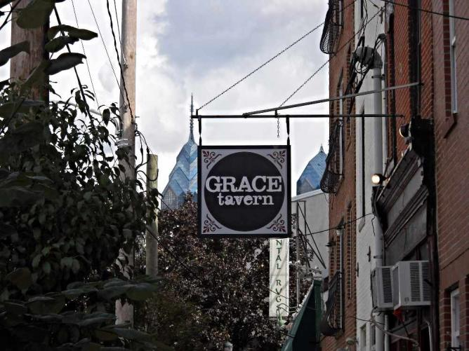The outside of Grace Tavern with a view of the Philadelphia skyline in the background.