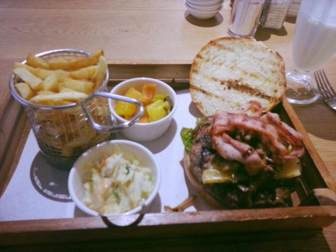 Beef burger topped with fried bacon served with fries, coleslaw and homemade pickles | Courtesy of Valerie Karuwa Wabungo