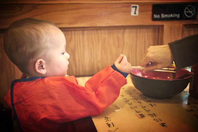 A young boy eats a ramen bowl at Spice C in Chinatown.