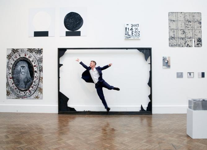 'The Royal Academy is the best cultural playground in the world,' declares Tim Marlow, playfully framed amongst artwork in the 2014 Summer Exhibition. Photograph by Robin Friend © Transglobe Publishing