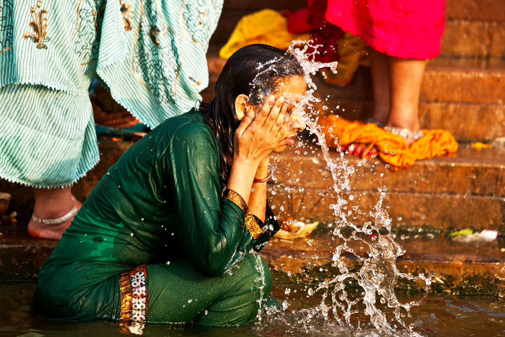 Unidentified woman washes her face in the river Ganges | © Travel Stock/Shutterstock