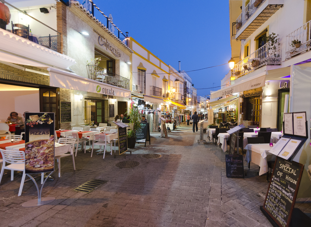People Strolling At Sunset Along The Pedestrian Area Full By Entertainment Facilities In Nerja Malaga