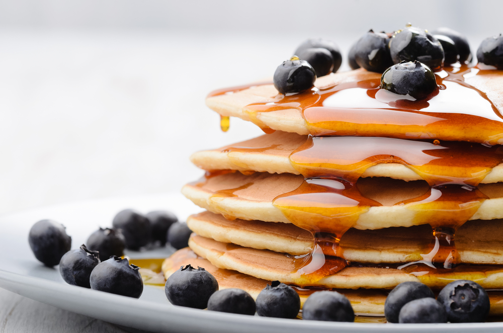 Delicious pancakes close up, with fresh blueberries and maple syrup © Daxiao Productions / Shutterstock