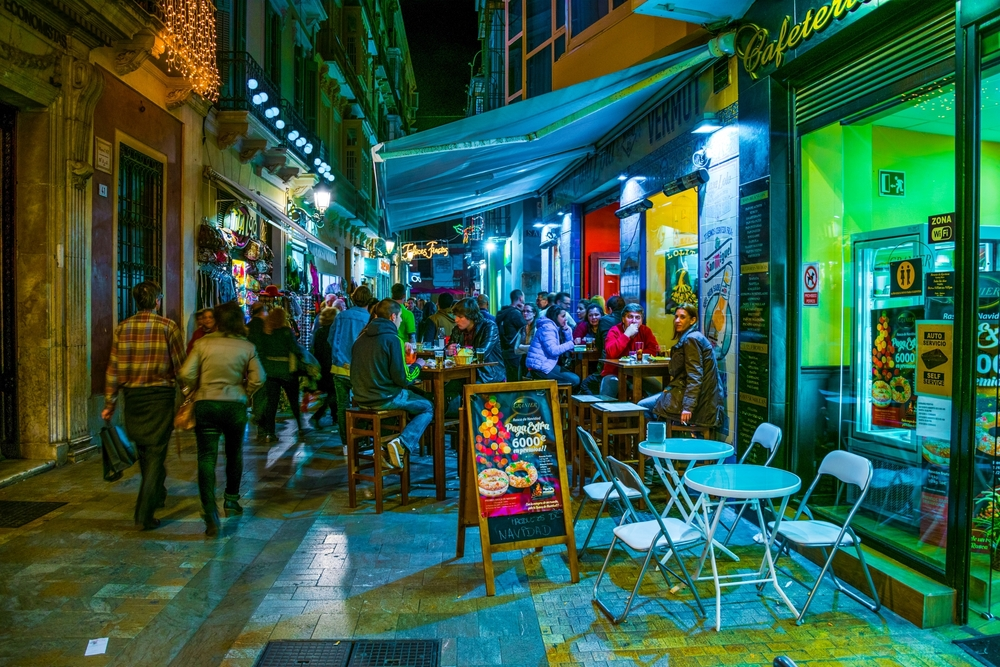 Crowds of tourists are strolling through the historical center of malaga after sunset © pavel dudek / Shutterstock