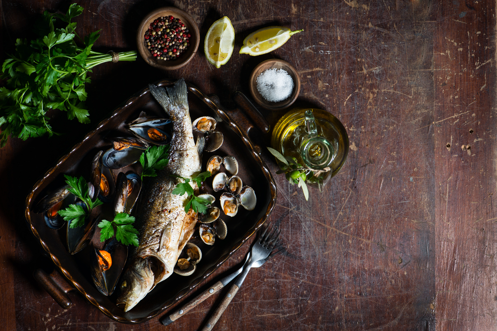 Roasted seabass and mussels in a dish on vintage wooden table with copy space © Iryna Denysova / Shutterstock