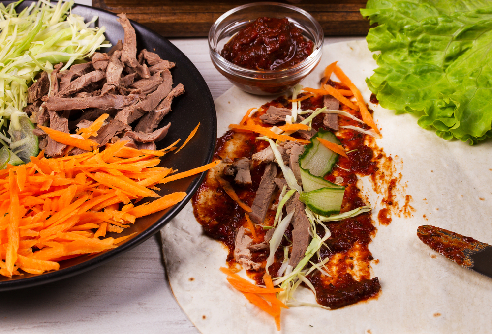 Shredded duck, carrot, cabbage, cucumber, salad, tomato sauce and flat bread | © freeskyline/Shutterstock