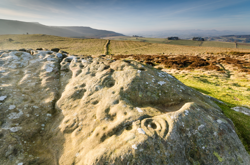 Prehistoric rock art / Ancient prehistoric cup and ring rock art is found on many stones at Lordenshaws in the Simonside Hills part of Northumberland National Park © Dave Head / Shutterstock