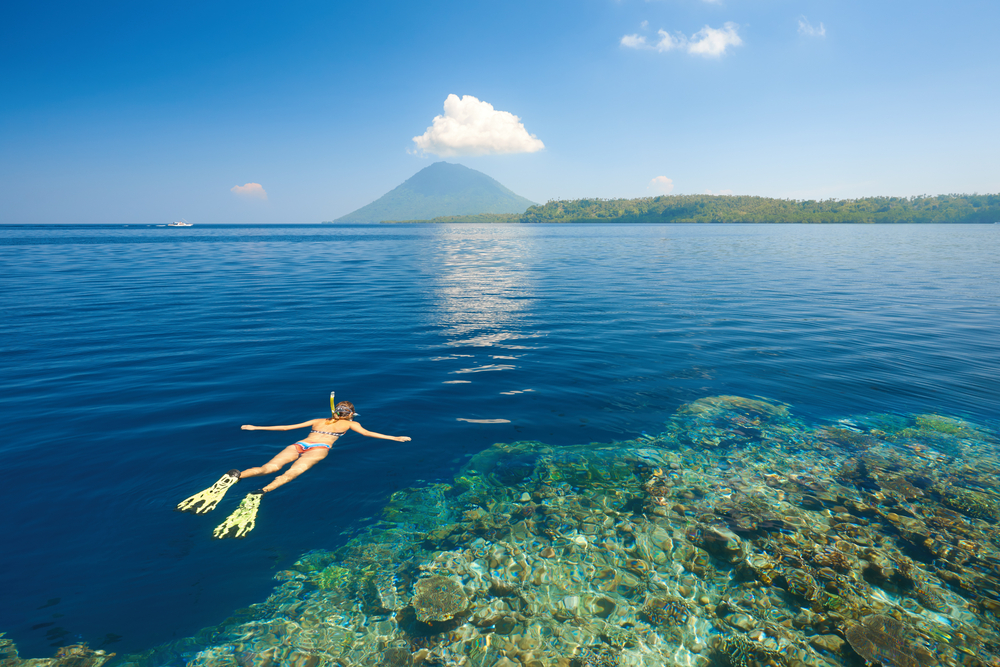 Snorkeling in blue and transparent tropical sea on a background volcano Manado Tua. North Sulawesi, Indonesia © soft_light / Shutterstock