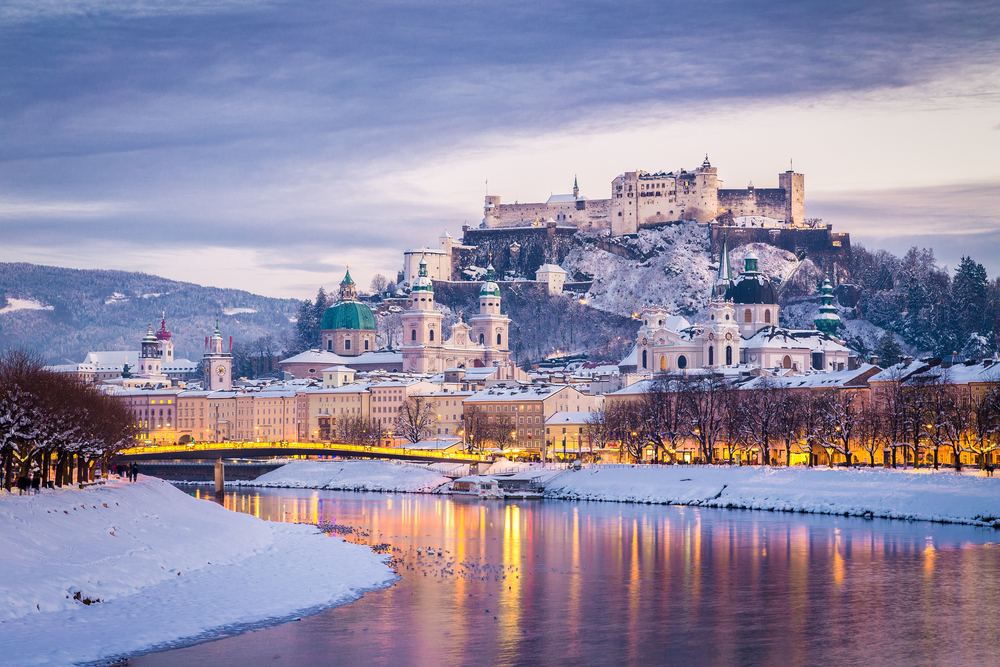Salzburg with famous Festung Hohensalzburg and Salzach river illuminated in beautiful twilight during scenic Christmas time © Canadastock / Shutterstock