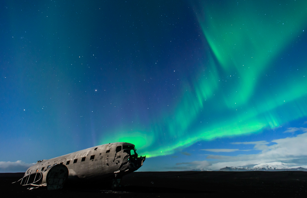 Plane wreckage on the beach, South Iceland. Green Aurora dancing in the sky over the abandoned plane © Supreecha Samansukumal / Shutterstock
