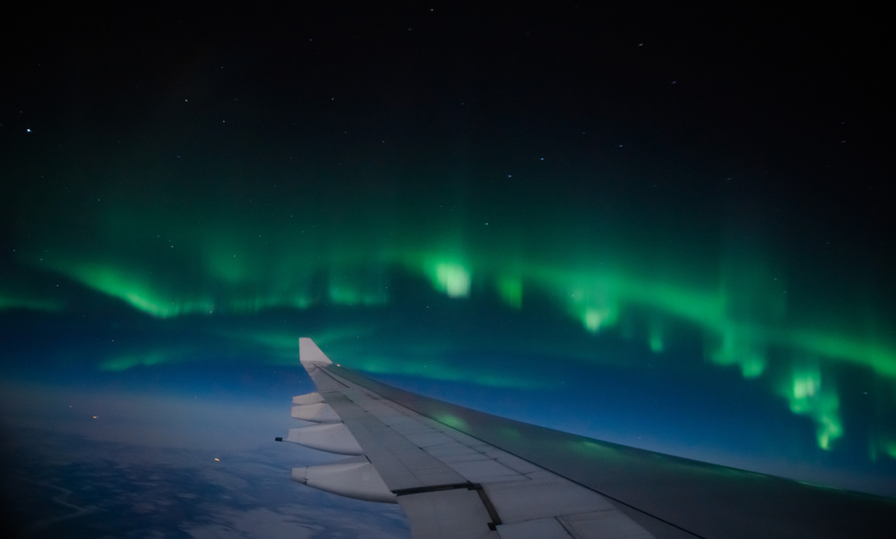 Aerial view of Northern Lights (Aurora Borealis) from an airplane flying over Northern hemisphere © Shaarila / Shutterstock
