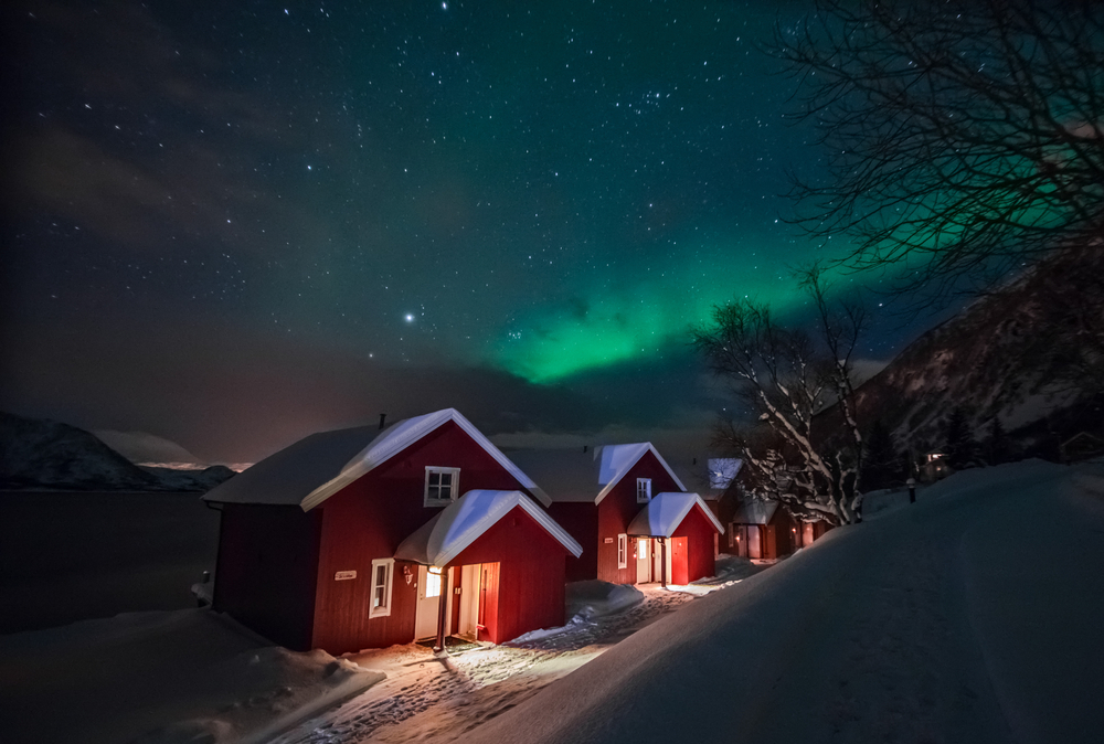 Northern lights (Aurora Borealis) over the red snowed-in cottages in Lapland village © Shaarila / Shutterstock