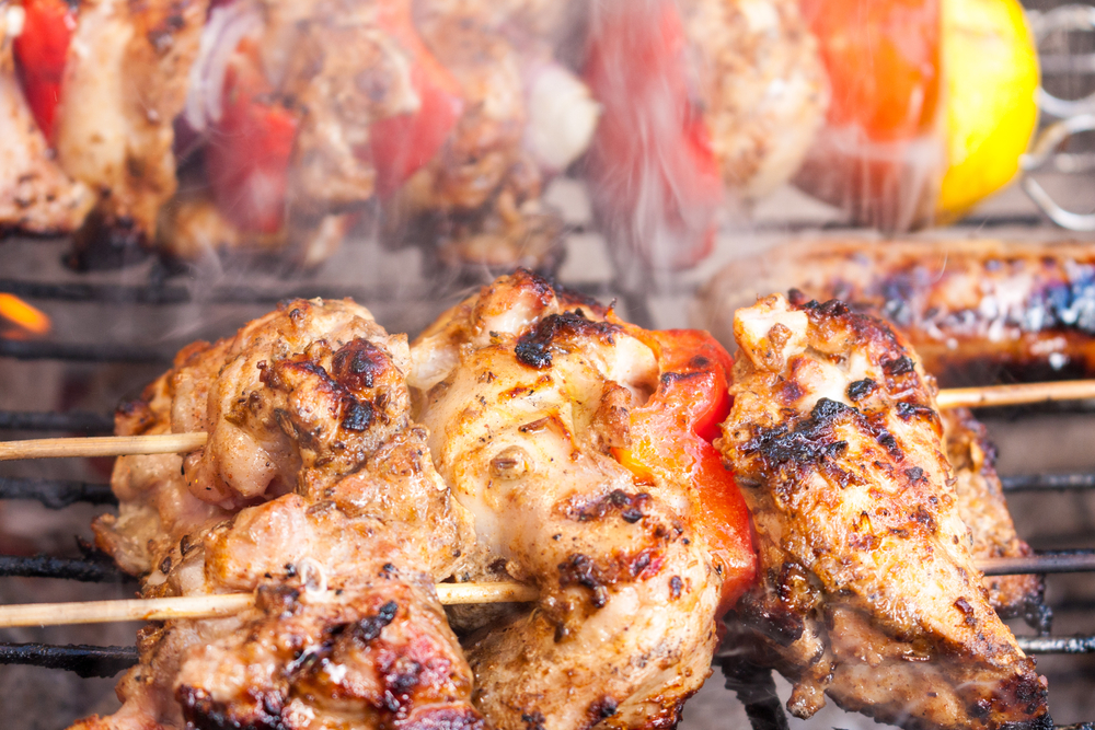 Chicken shawarma kebab skewer gently cooking on a smoking barbecue ©Timages / Shutterstock