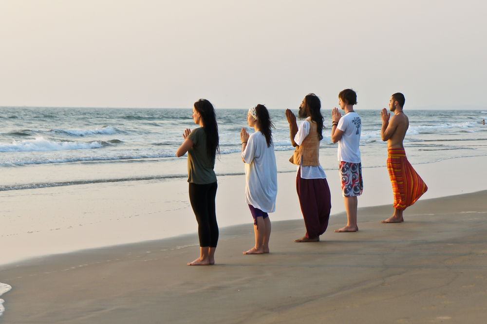 ndian yoga master and his international students meditate at sunset on the Goa beach, India | © Vladimir Zhoga/Shutterstock