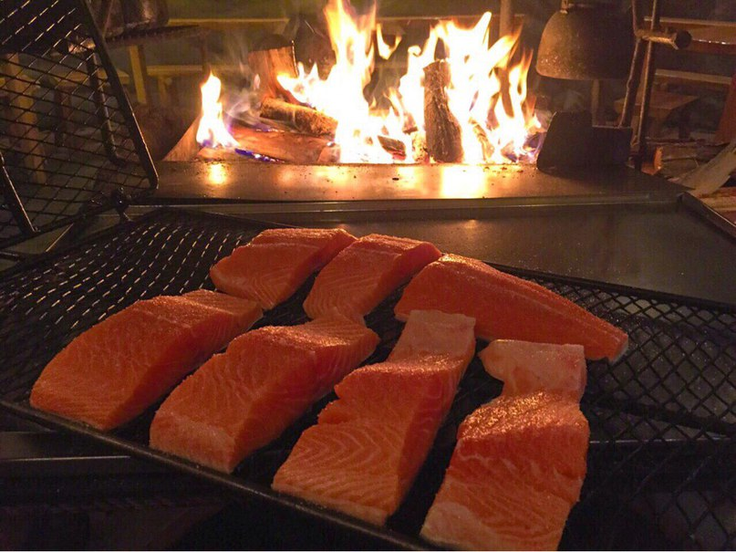 Fresh Salmon Going Into The Fire | Image Courtesy of Santa's Salmon Place