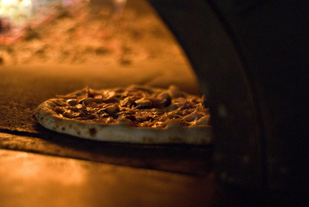 Pizza Baking in Wood Burning Oven | ©N Wong/Flickr
