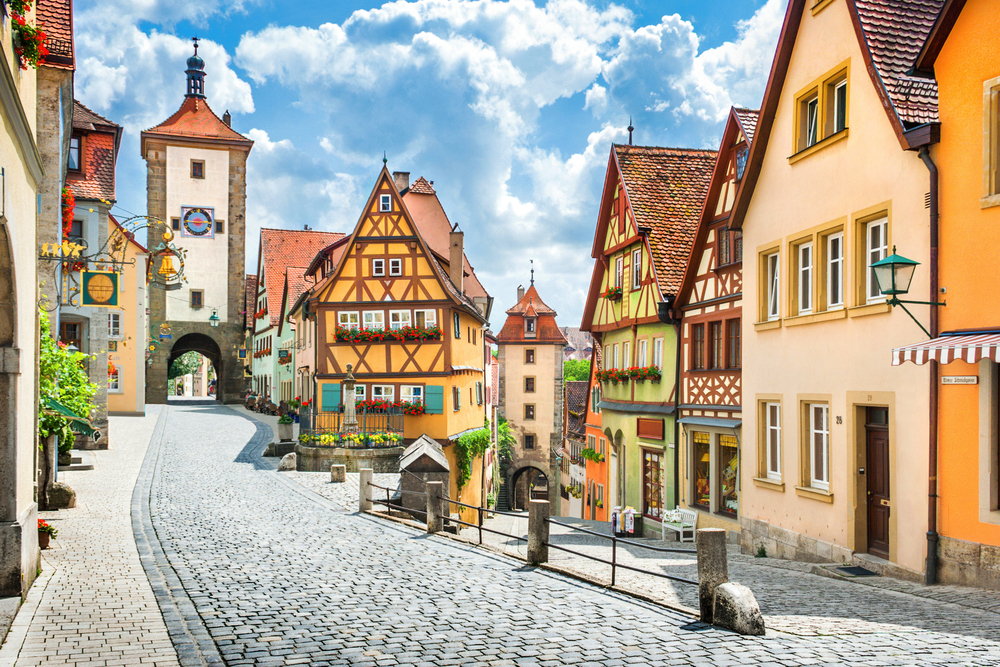 Beautiful postcard view of the famous historic town of Rothenburg ob der Tauber on a sunny day with blue sky and clouds in summer, Franconia, Bavaria, Germany | © Canadastock/Shutterstock