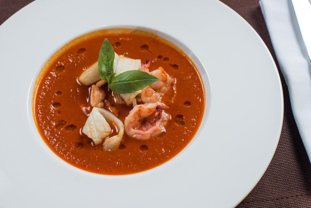 French Bouillabaisse fish soup with seafood, salmon fillet, shrimp, rich taste, tasty dinner © Suvorov_Alex / Shutterstock