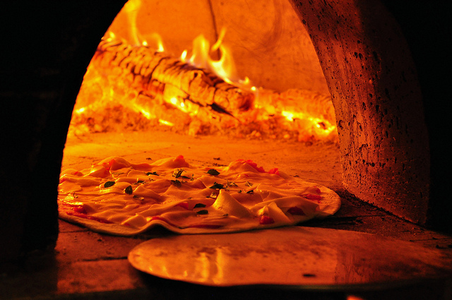 Pizza baking in wood fire oven I ©Andre Roberto Doreto Santos/Flickr