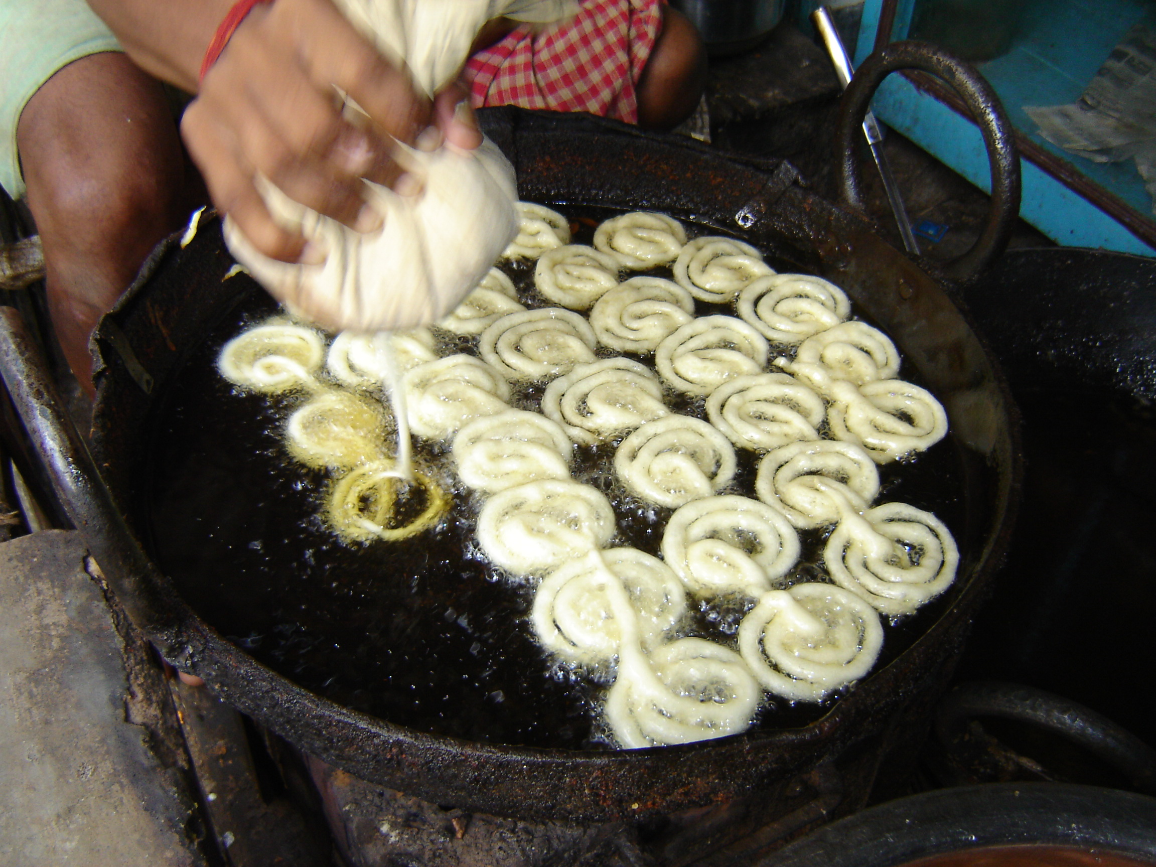 Preparing a fresh jalebi at the market / © wikicommons