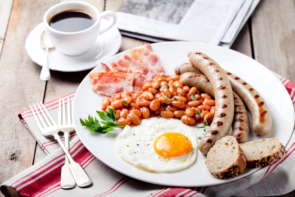 Fried egg with beans in tomato sauce, bacon and grilled sausages with a cup of coffee and morning newspaper © Anna_Pustynnikova / Shutterstock