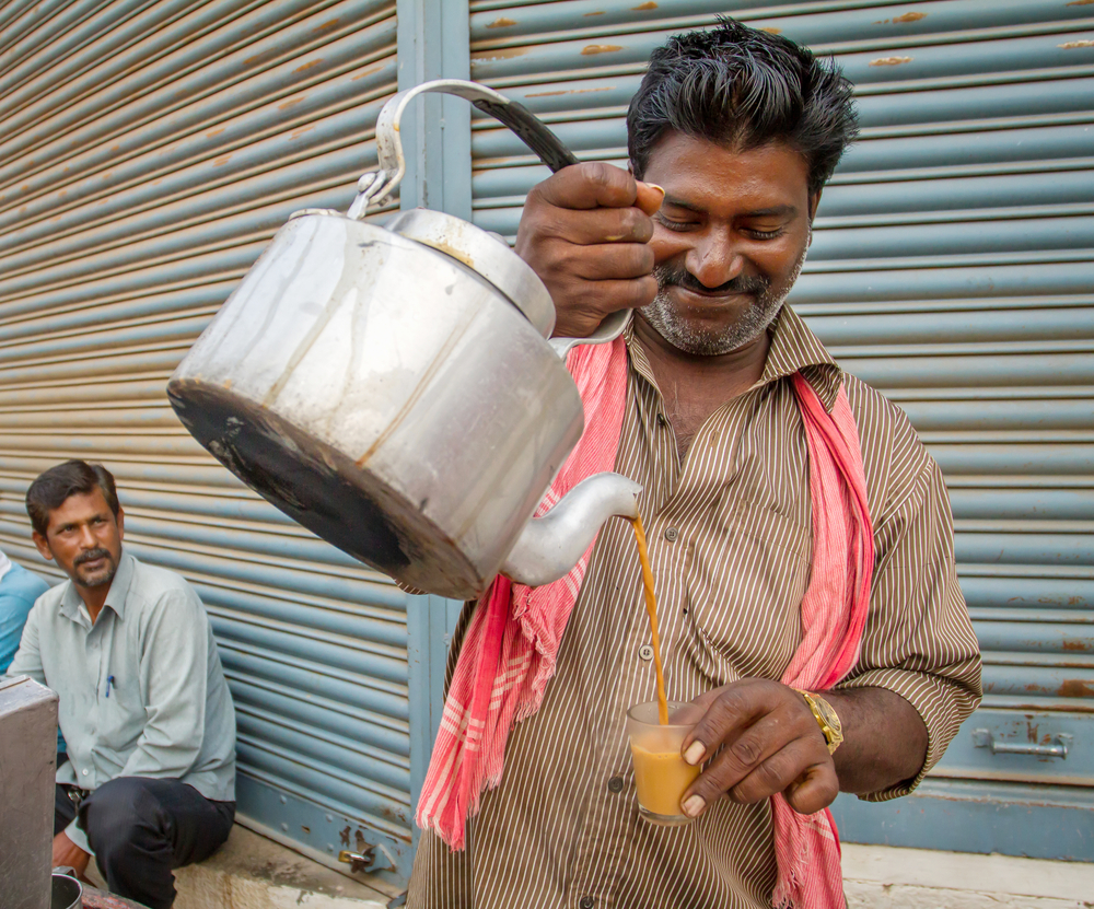 Men pours cup hot milk tea Indian style or chai for customers from his shop along street © Alexander Mazurkevich / Shutterstock