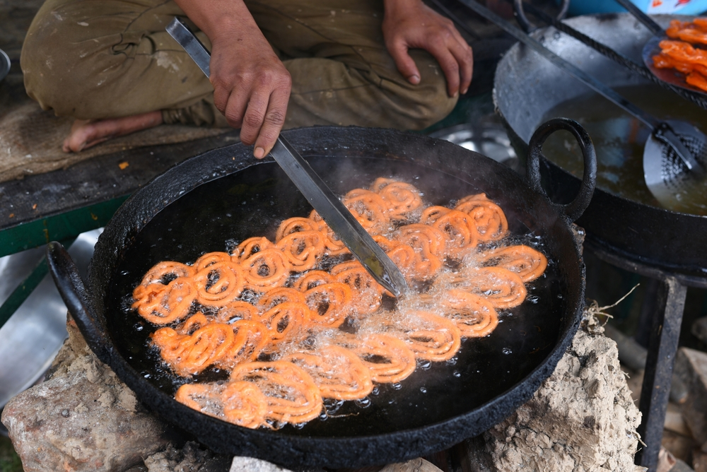 Indian jalebi sweet at a street stall, yummy street food © Singh_lens / Shutterstock
