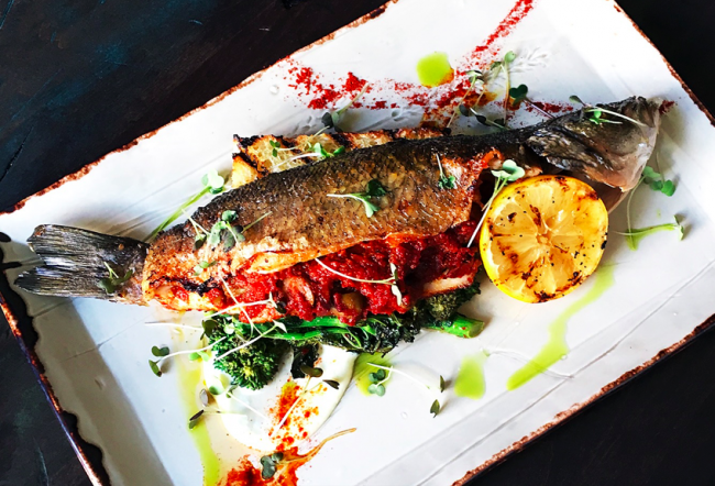 Signature Branzino with sugo puttanesca, spiced rapini, grilled house-made focaccia | Image courtesy of Lake Road Restaurant