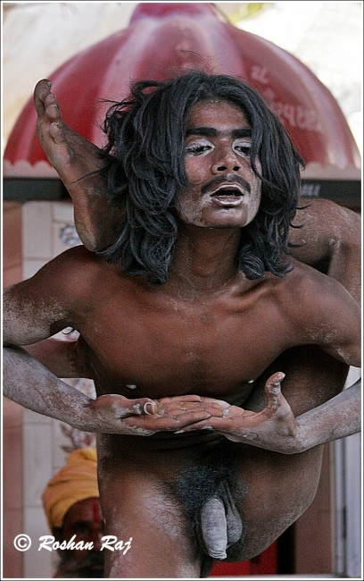 Naga Sadhu assuming a yoga pose for the photographer |© Flickr/Roshan Raj