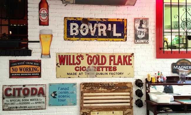 Antique enamel signs in the patio area at The Irish Bank © Brixton Key
